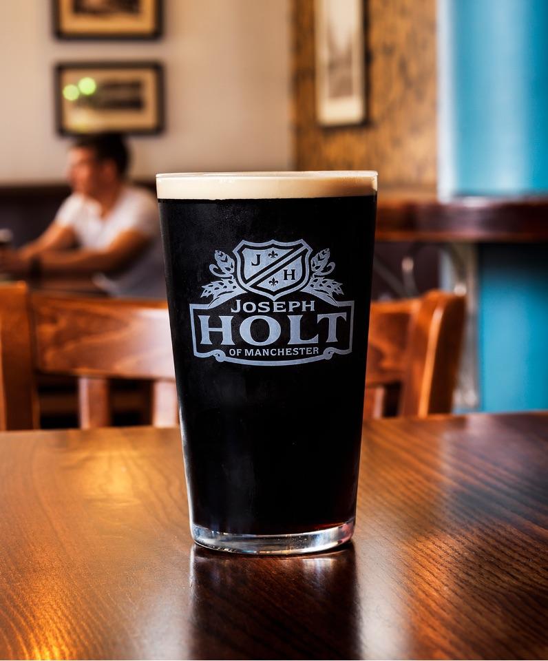 joseph holt black ale pint glass on table