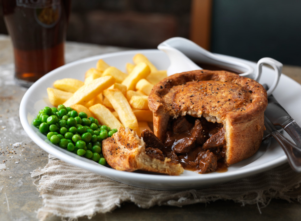 steak pie chips and peas on a plate