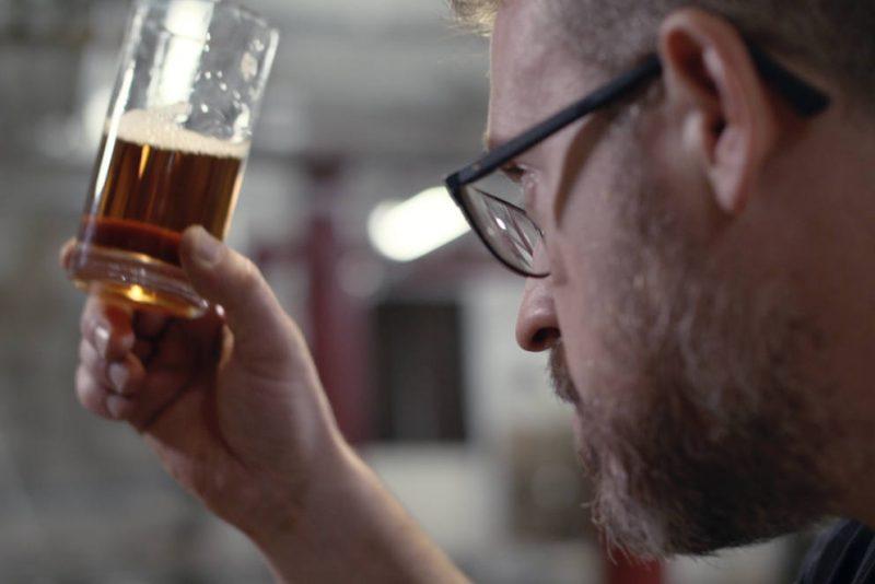 joseph holt team brewer raising beer glass